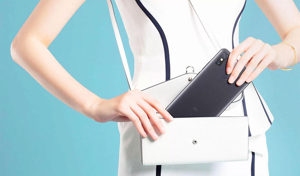 Девушка кладет Xiaomi Mi Max 3 в сумочку